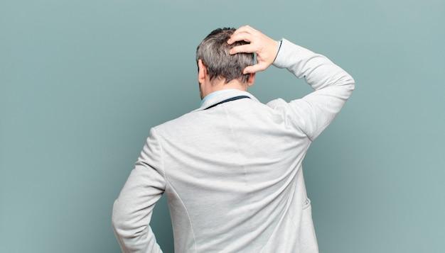 Volwassen zakenman die zich geen idee en verward voelt, een oplossing denkt, met de hand op de heup en de andere op het hoofd