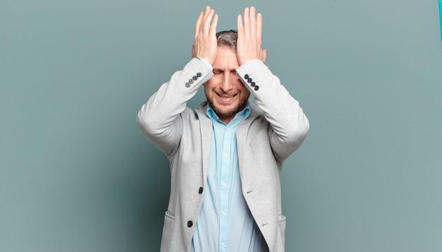 Volwassen zakenman die zich gestrest en angstig, depressief en gefrustreerd voelt door hoofdpijn, beide handen naar het hoofd opsteken