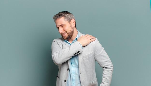 Volwassen zakenman die zich moe, gestrest, angstig, gefrustreerd en depressief voelt, rug- of nekpijn heeft