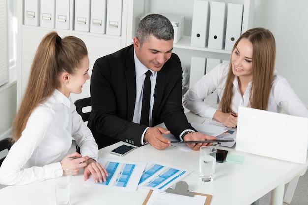 Volwassen zakenman die zijn jonge vrouwelijke collega's raadpleegt tijdens zakelijke bijeenkomst. partners bespreken documenten en ideeën