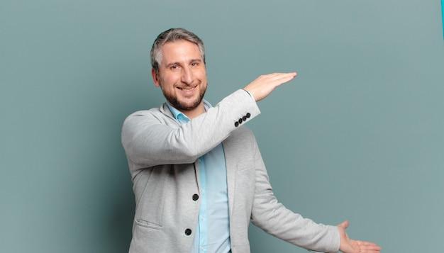 Volwassen zakenman glimlacht, voelt zich gelukkig, positief en tevreden, houdt of toont object of concept op kopieerruimte