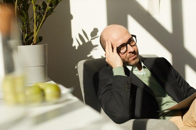 Volwassen zakenman in brillen zittend op een stoel en documenten lezen tijdens het werken op kantoor