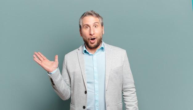 Volwassen zakenman kijkt verbaasd en geschokt, met open mond naar beneden terwijl hij een voorwerp vasthoudt met een open hand op de zijkant
