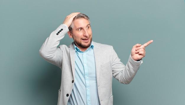 Volwassen zakenman lacht, kijkt blij, positief en verrast, realiseert zich een geweldig idee wijzend naar laterale kopie ruimte