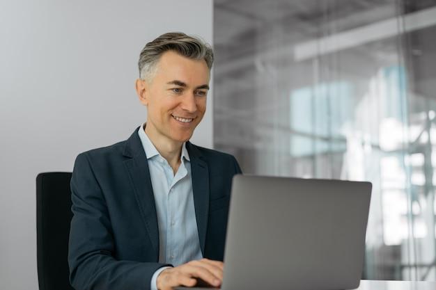 Volwassen zakenman met behulp van laptop online werken zittend in kantoor. portret van succesvolle glimlachende programmeur op de werkplek