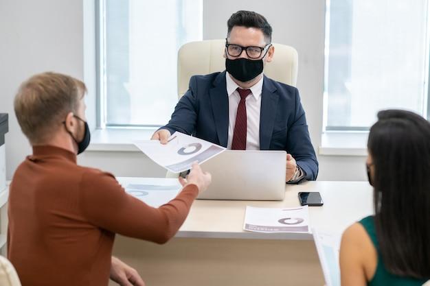 Volwassen zakenman met beschermend masker papier doorgeven aan jonge man