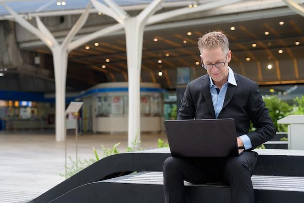 Volwassen zakenman met bril met behulp van laptop in de straten van de stad buitenshuis