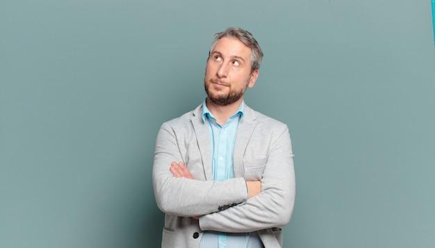 Volwassen zakenman met een bezorgde, verwarde, onwetende uitdrukking, opkijkend om ruimte te kopiëren, twijfelend