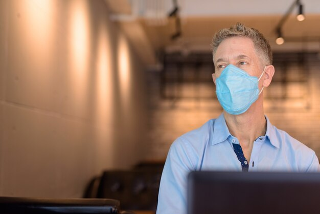 Volwassen zakenman met masker denken tijdens het gebruik van laptop in de coffeeshop