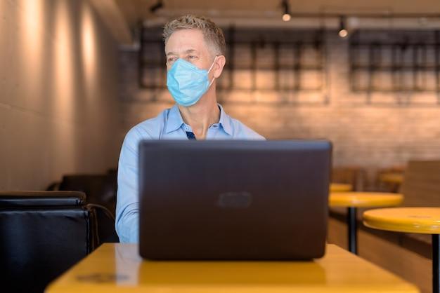 Volwassen zakenman met masker denken tijdens het gebruik van laptop in de koffieshop
