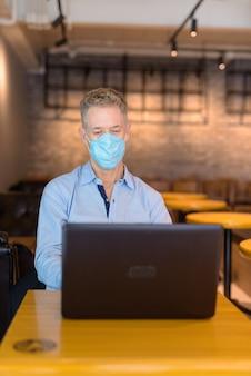Volwassen zakenman met masker met behulp van laptop tijdens de vergadering in de coffeeshop
