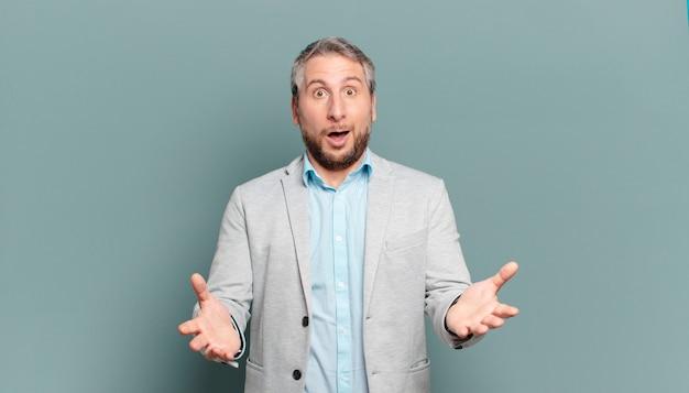 Volwassen zakenman met open mond en verbaasd, geschokt en verbaasd met een ongelooflijke verrassing