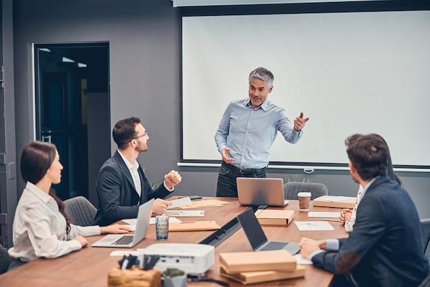 Volwassen zakenman praten met collega in bestuurskamer