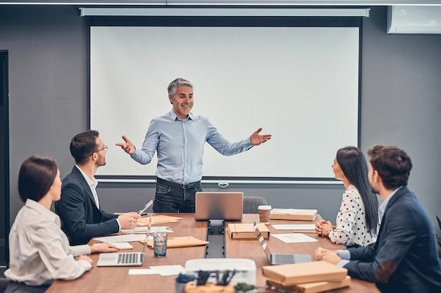 Volwassen zakenman verwelkomt zijn team tijdens de vergadering
