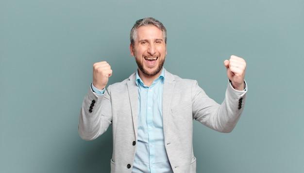 Volwassen zakenman voelt zich gelukkig, positief en succesvol, viert overwinning, prestaties of veel geluk
