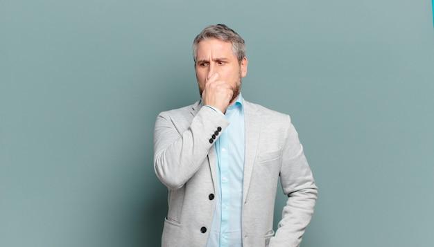 Volwassen zakenman walgt en houdt zijn neus vast om te voorkomen dat hij een vieze en onaangename stank ruikt