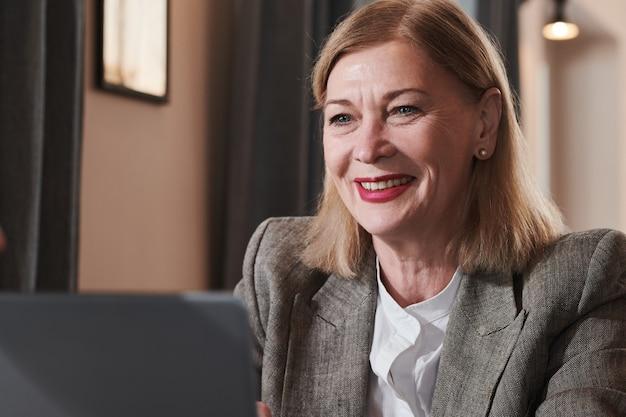 Volwassen zakenvrouw kijken naar computermonitor en glimlachend werken op kantoor