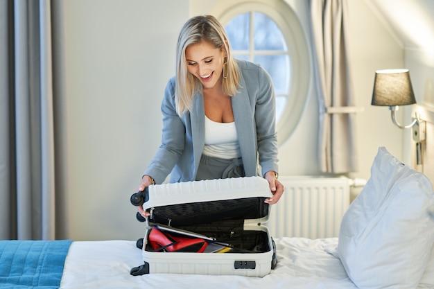 Volwassen zakenvrouw koffer uitpakken in hotelkamer