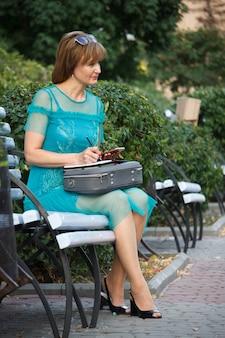 Volwassen zakenvrouw van middelbare leeftijd zittend op een bankje en maakt aantekeningen in een notitieblok, controleren met een smartphone