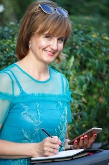 Volwassen zakenvrouw van middelbare leeftijd zittend op een bankje en maakt aantekeningen in een notitieblok.