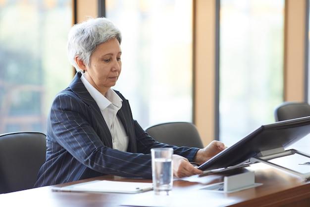 Volwassen zakenvrouw zittend aan tafel en het gebruik van computer tijdens seminar in directiekamer