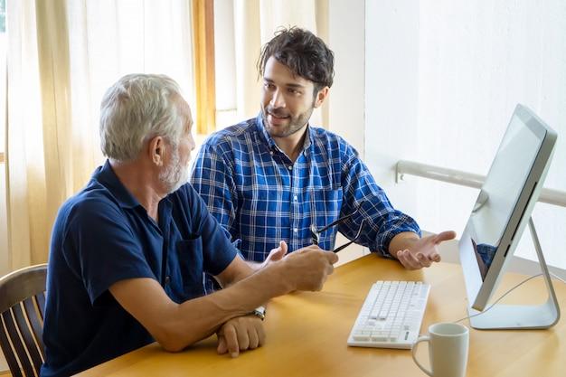 Volwassen zoon die oude vader onderwijst aan het gebruiken van computer