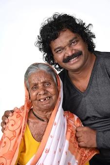 Volwassen zoon en zijn bejaarde moeder. india senior vrouw met haar zoon op witte achtergrond