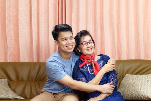 Volwassen zoon komt thuis en knuffel moeder op de moederdag