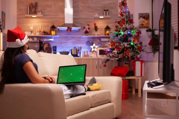 Volwassene die comfortabel op de bank ligt met een groen scherm mock-up chroma key laptop
