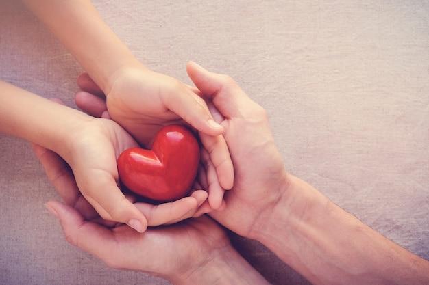 Volwassene en kind handen holiding rood hart, gezondheidszorg liefde, geven, hoop en familie concept