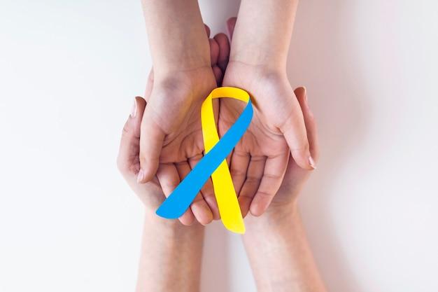 Volwassene en kind handen met blauw en geel lint, bewustzijn van het syndroom van down