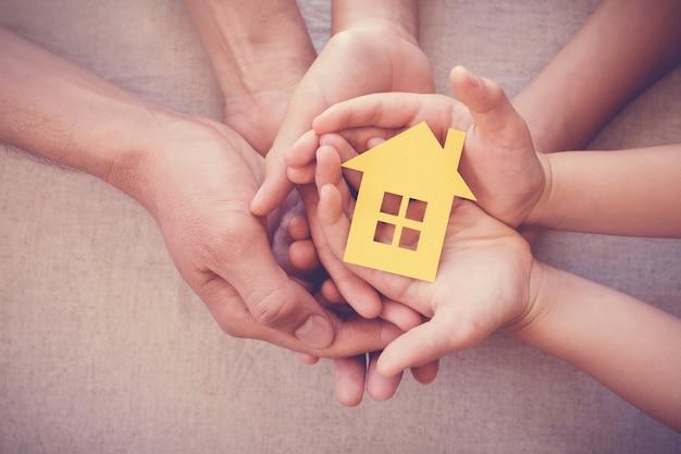 Volwassene en kind handen met gele huis, familie thuis en dakloze onderdak concept
