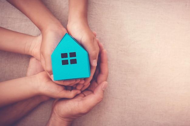 Volwassene en kind handen met witte huis, familie thuis en dakloze onderdak concept