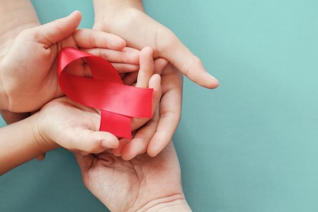 Volwassene en kinderenhanden die rood lint op rode achtergrond, hiv voorlichtingsconcept, de dag van wereldaids, de dag van wereldhypertensie houden