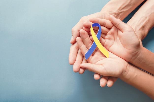 Volwassene en kindhanden die blauw en geel lint gevormd document houden