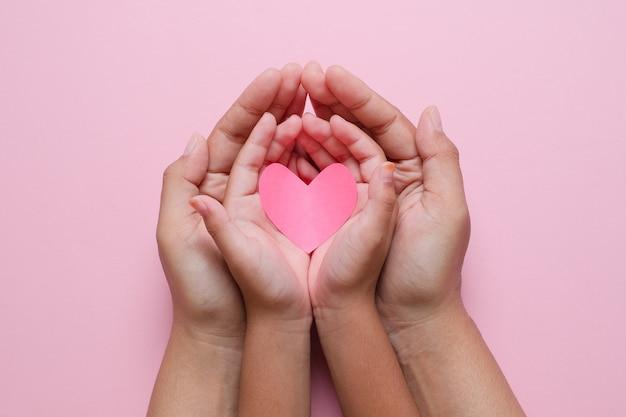 Volwassene en kindhanden die rood hart over roze achtergrond houden. liefde, gezondheidszorg, familie, verzekering, donatieconcept