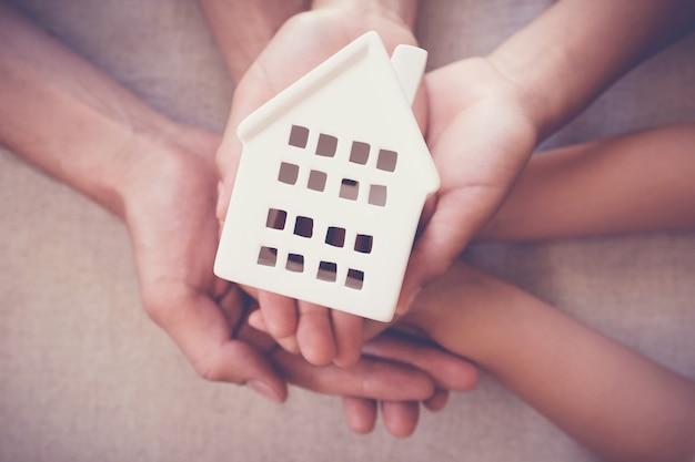 Volwassene en kindhanden die wit huis houden