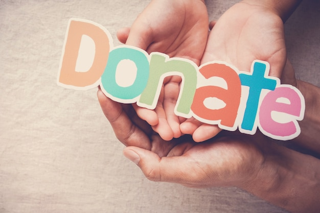 Volwassene en kindhanden die woord doneren, schenking en liefdadigheidsconcept houden