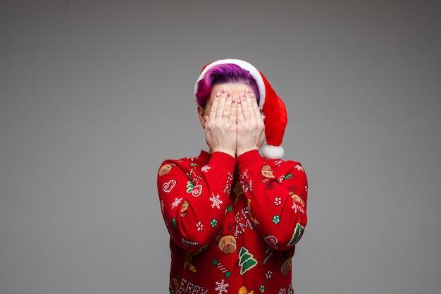 Volwassene, gekleed in rode kerstkleren, staat alleen en bedekt het gezicht met twee handen. nieuwjaar concept