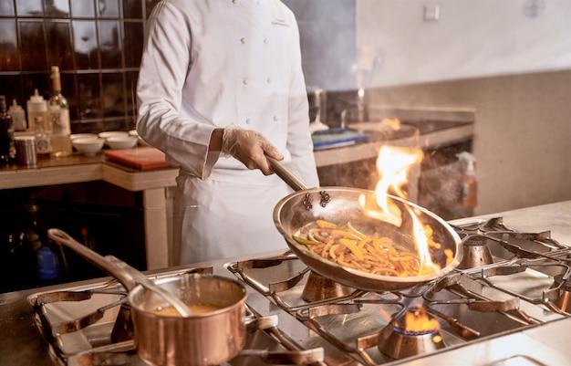 Volwassene in wit chef-kokuniform schudt een pan met plakjes peper die erin vlam vatten boven het fornuis