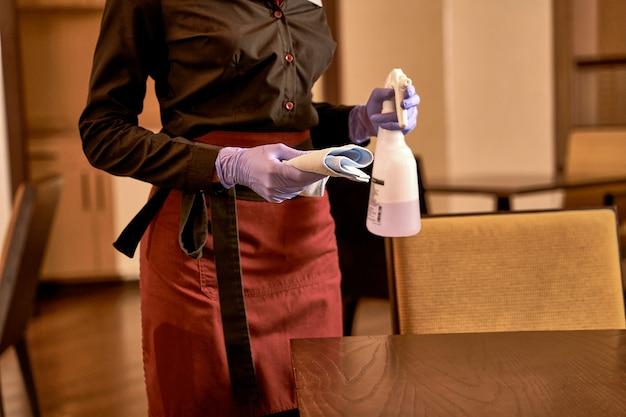 Volwassene staat links aan de tafel en houdt een opgevouwen stuk doek vast terwijl hij een sproeier met reinigingsvloeistof draagt
