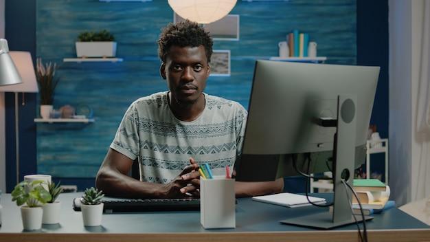 Volwassene van afrikaanse etniciteit die computer gebruikt voor werken op afstand