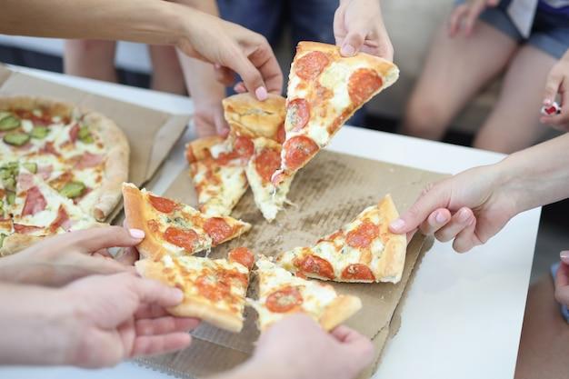 Volwassenen en kinderen nemen een stuk pizza op de doos