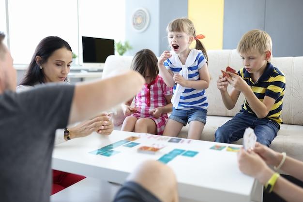 Volwassenen en kinderen zitten aan tafel en houden speelkaarten vast. meisje stond op en schreeuwt.