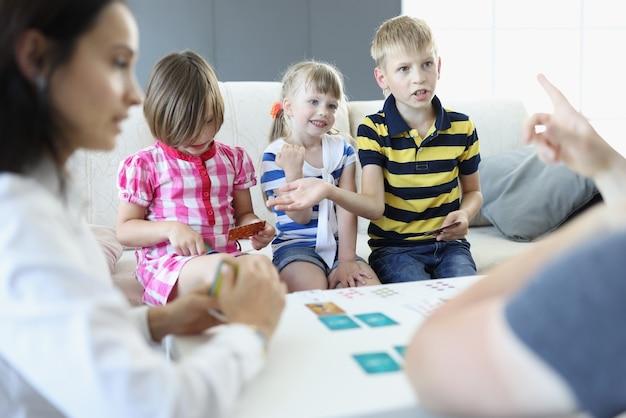 Volwassenen en kinderen zitten rond een tafel waarop speelkaarten liggen. de jongen maakt ruzie en bespreekt de regels met een volwassene.