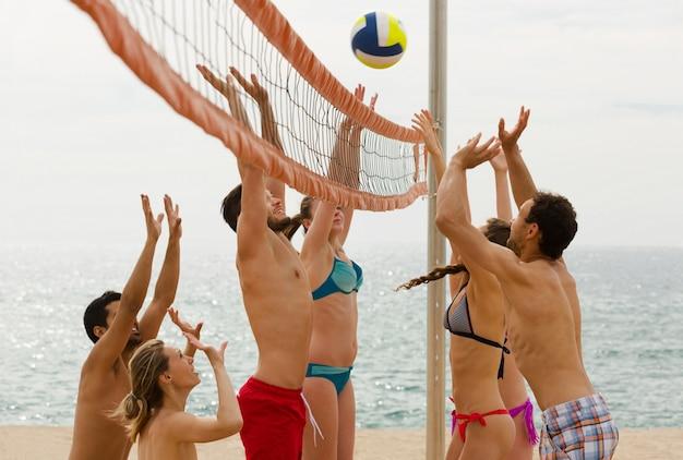 Volwassenen gooien bal over net en lachen