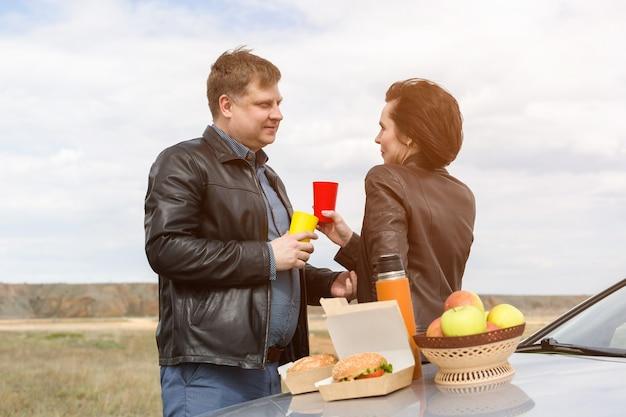 Volwassenen hadden een romantische picknick bij de auto.