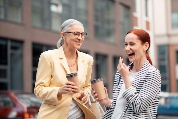 Voor altijd vrienden. close-up portret van twee gelukkige blanke moderne aantrekkelijke zakenvrouwen die lachen terwijl ze buiten staan