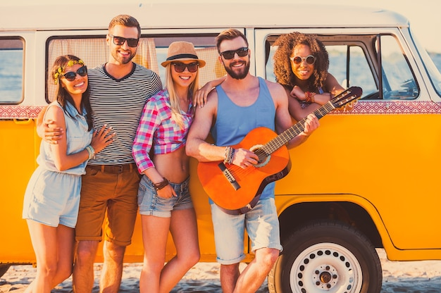 Voor altijd vrienden. groep jonge vrolijke mensen die in de buurt van hun retro minibus staan en glimlachen
