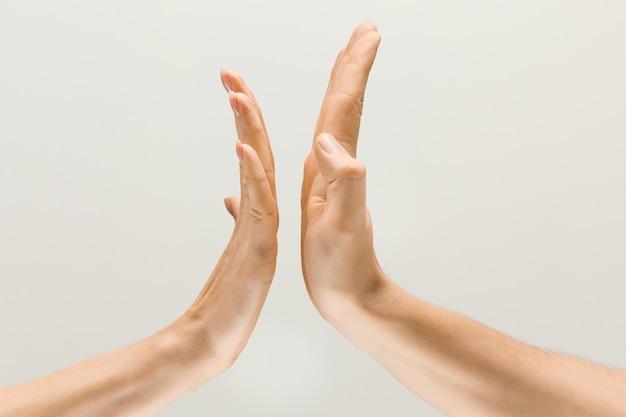 Voor altijd vrienden. mannelijke en vrouwelijke handen die een gebaar van het krijgen van aanraking of groeten demonstreren die op grijze studioachtergrond worden geïsoleerd. concept van menselijke relaties, relatie, gevoelens of zaken.